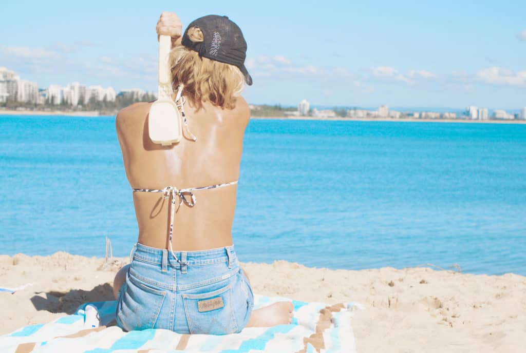 Female using bakslap apply sunscreen on her back